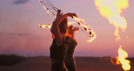 pirotecnia : Fire dancers against sunset. A young woman poses with her fire hoop against the sunset during her dance performance.