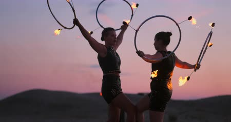 pirotecnia : Women with fire at sunset on the sand dance and show tricks against the beautiful sky in slow motion. Vídeos