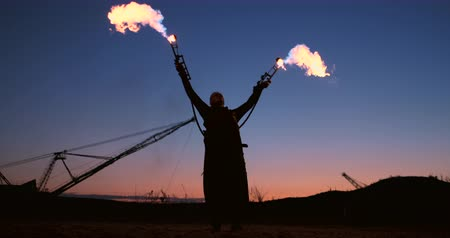 fire arms : A man with a flamethrower at sunset in slow motion. Costume for zombie Apocalypse and Halloween. Stock Footage