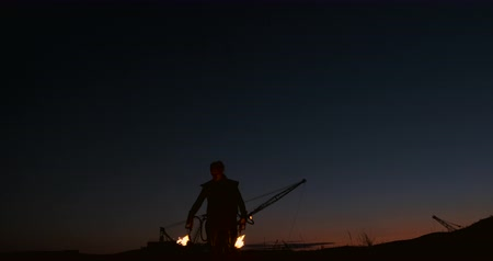 arma de fogo : A man in a raincoat with two flamethrowers lets out a fiery flame standing at sunset on the sand.