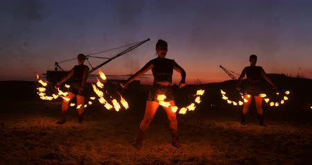 トーチ : A group of men and woman fire show at night on the sand against the background of fire and tower cranes