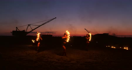 akrobata : Fire show three women in their hands twist burning spears and fans in the sand with a man with two flamethrowers in slow motion.