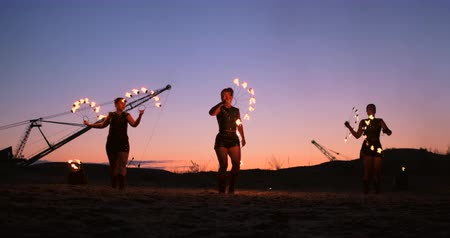 spinner : Fire show three women in their hands twist burning spears and fans in the sand with a man with two flamethrowers in slow motion.