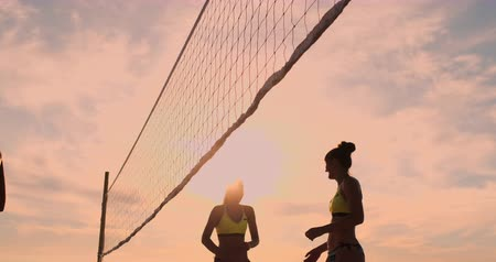 bumps : Group of young girls playing beach volleyball during sunset or sunrise, slow motion,