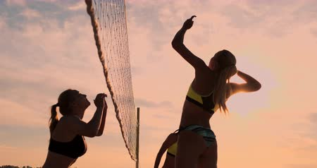knock : Group of young girls playing beach volleyball during sunset or sunrise. Stock Footage