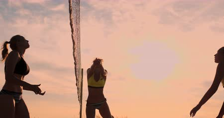 voleybol : Group of young girls playing beach volleyball during sunset or sunrise, slow motion,