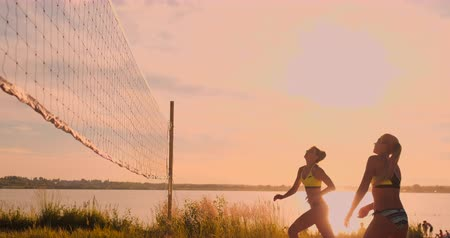kopogás : Group of young girls playing beach volleyball during sunset or sunrise. Stock mozgókép