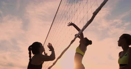 reprise de volée : Sexy girls volleyball players pass the ball near the net and hit the ball at sunset in slow motion