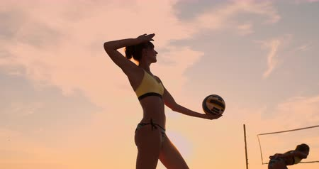 smashing : Beach volleyball serve - woman serving in beach volley ball game. Overhand spike serve. Young people having fun in the sun living healthy active sports lifestyle outdoors.