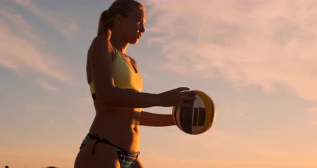 volleyball : Athletic girl playing beach volleyball jumps in the air and strikes the ball over the net on a beautiful summer evening. Caucasian woman score a point Stock Footage