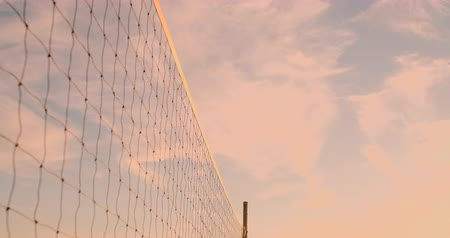 volleyball : Beach volleyball match girls hit the ball in slow motion at sunset on the sand.
