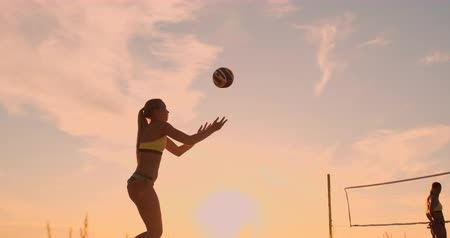versenyez : Athletic girl playing beach volleyball jumps in the air and strikes the ball over the net on a beautiful summer evening. Caucasian woman score a point Stock mozgókép