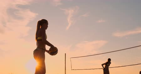 voleybol : Beach volleyball serve - woman serving in beach volley ball game. Overhand spike serve. Young people having fun in the sun living healthy active sports lifestyle outdoors.