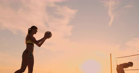 volleyball : A beautiful woman in a bikini with a ball at sunset is getting ready to do serve jump on the beach in a volleyball match on the sand. Stock Footage
