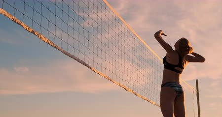 atleta : Beautiful bikini girls on the beach play volleyball in slow motion.