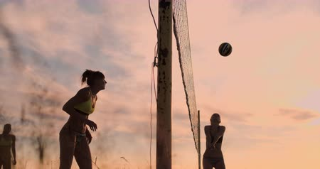 voleybol : Beautiful bikini girls on the beach play volleyball in slow motion.