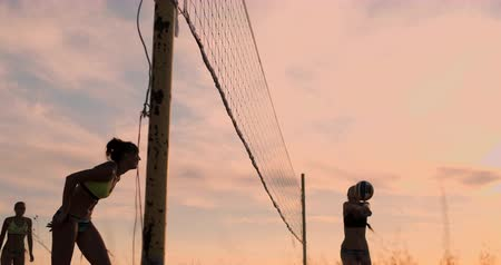 залп : Sexy volleyball girls in bikini play on the beach in summer volleyball on the sand at sunset in slow motion.