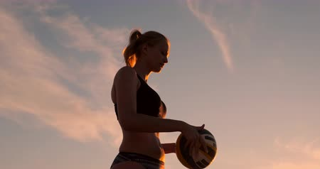 voleybol : A beautiful woman in a bikini with a ball at sunset is getting ready to do serve jump on the beach in a volleyball match on the sand. Stok Video