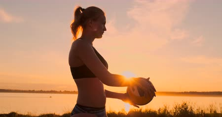 voleybol : Athletic girl playing beach volleyball jumps in the air and strikes the ball over the net on a beautiful summer evening. Caucasian woman score a point Stok Video