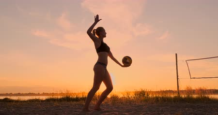 volleyball players : Athletic girl playing beach volleyball jumps in the air and strikes the ball over the net on a beautiful summer evening. Caucasian woman score a point Stock Footage