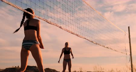 volleyball : Young female volleyball players pass and spike the ball over the net on a sunny summer evening. Fit Caucasian girls playing beach volleyball at sunset Stock Footage