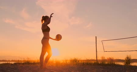 knock : Young girl jump serve volleyball on the beach, slow motion.