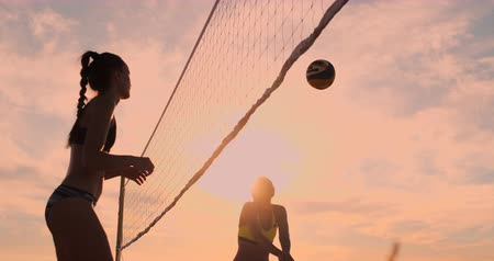 volleyball players : SLOW MOTION, LOW ANGLE, CLOSE UP, SUN FLARE: Athletic girl playing beach volleyball jumps in the air and strikes the ball over the net on a beautiful summer evening. Caucasian woman score a point