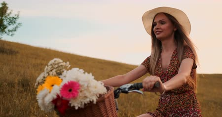 педаль : Happy girl with a bouquet of flowers riding a bike in a hat and a summer short dress.