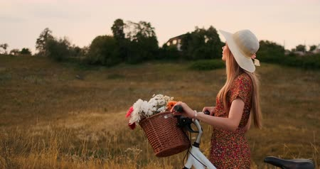wildflowers : Young smiling blonde in hat and dress walking in dress with bike and flowers in basket.