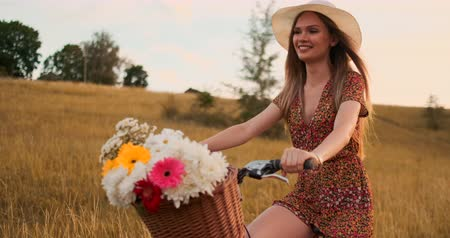 ciclo di vita : Middle plan is the Blonde in the hat rides a bike with flowers and smiles.