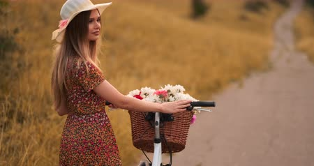 egyetlen virág : A girl in a hat with a Bicycle turns around and looks at the camera smiling.