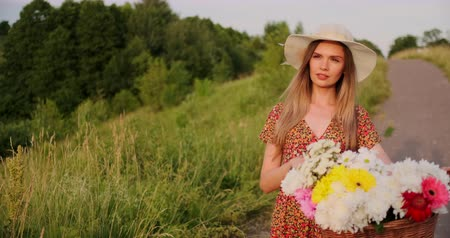 egyetlen virág : Middle plan girl in dress goes with bike and flowers in the field.