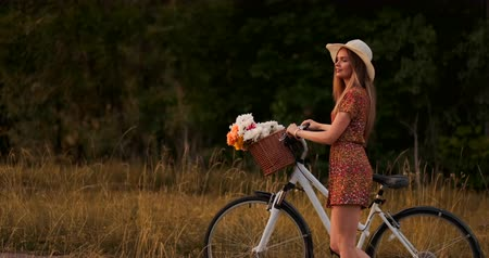 wildflowers : Side view: smiling girl in a dress walking with a bike in the summer on the handlebar basket with wildflowers.