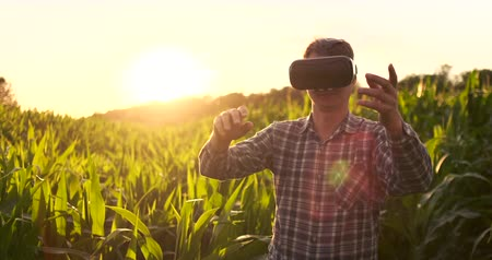 hidrasyon : Smart farming with IoT, futuristic agriculture concept : Farmer wears VR or AR glasses while monitoring rainfall, temeprature, humidity, soil pH with immersive experience on digital holographic screen