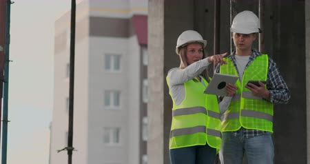 architekt : Construction worker man and architect woman in a helmet, discuss the plan of construction of house, tell each other about the design, holding a tablet, look at the drawings, background of sun rays