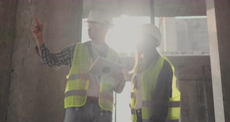 предпринимателей : Engineers or architects have a discussion at construction site looking through the plan of construction. contre jour. Engineers or architects have a discussion.