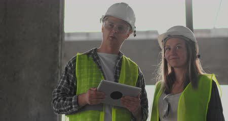 workgroup : Two engineers a man and a woman with a tablet computer at a construction site condemn the construction plan of the building