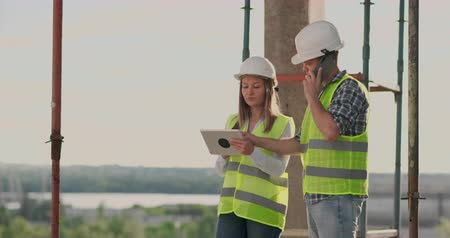 main d oeuvre : Building in construction with a female and a male builders, constructors, engineers walking along it. Vidéos Libres De Droits