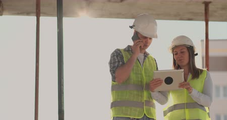 ev idaresi : The controller is a man of a building under construction talking on the phone with management and has discussed with the engineer and architect woman construction progress