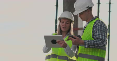workman : Building in construction with a female and a male builders, constructors, engineers walking along it. Stock Footage