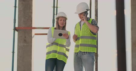 cartografia : Building in construction with a female and a male engineers using a tablet and mobile phone to visualize the building plan. Vídeos