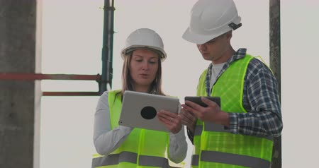 kusy : Building in construction with a female and a male engineers using a tablet and mobile phone to visualize the building plan. Dostupné videozáznamy