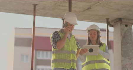 тачпад : Supervisor of a building under construction man discussing with engineer designer woman the progress of construction and examines a building plan