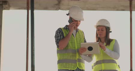 incompleto : Building in construction with a female and a male engineers using a tablet and mobile phone to visualize the building plan. Stock Footage