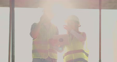 realty : Building in construction with a female and a male builders, constructors, engineers walking along it. Stock Footage