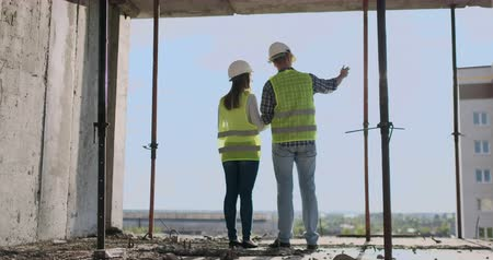 economical : couple of engineer or technician man and woman with safety helmet holding mobile radio phone planning about building plan to greeting start up project in construction site building, industry concept.