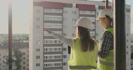 architekt : Back view young foreman and engineer checking the blueprint and talking about construction project with commitment to success at construction site.