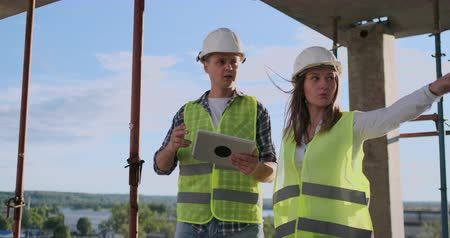 inspektor : Building technology and people concept - smiling builders in hardhats with tablet pc computer outdoors.