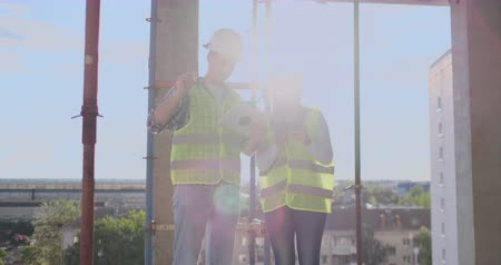 constructing : Building technology and people concept - smiling builders in hardhats with tablet pc computer outdoors.