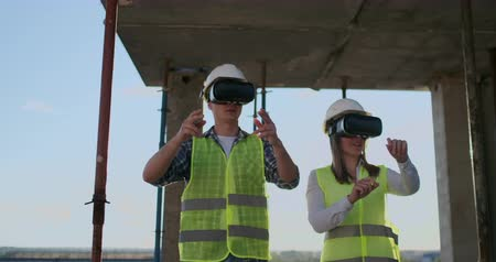 inacabado : Two contemporary crew workers using VR to visualize projects standing in unfinished building on construction site, copy space. Stock Footage